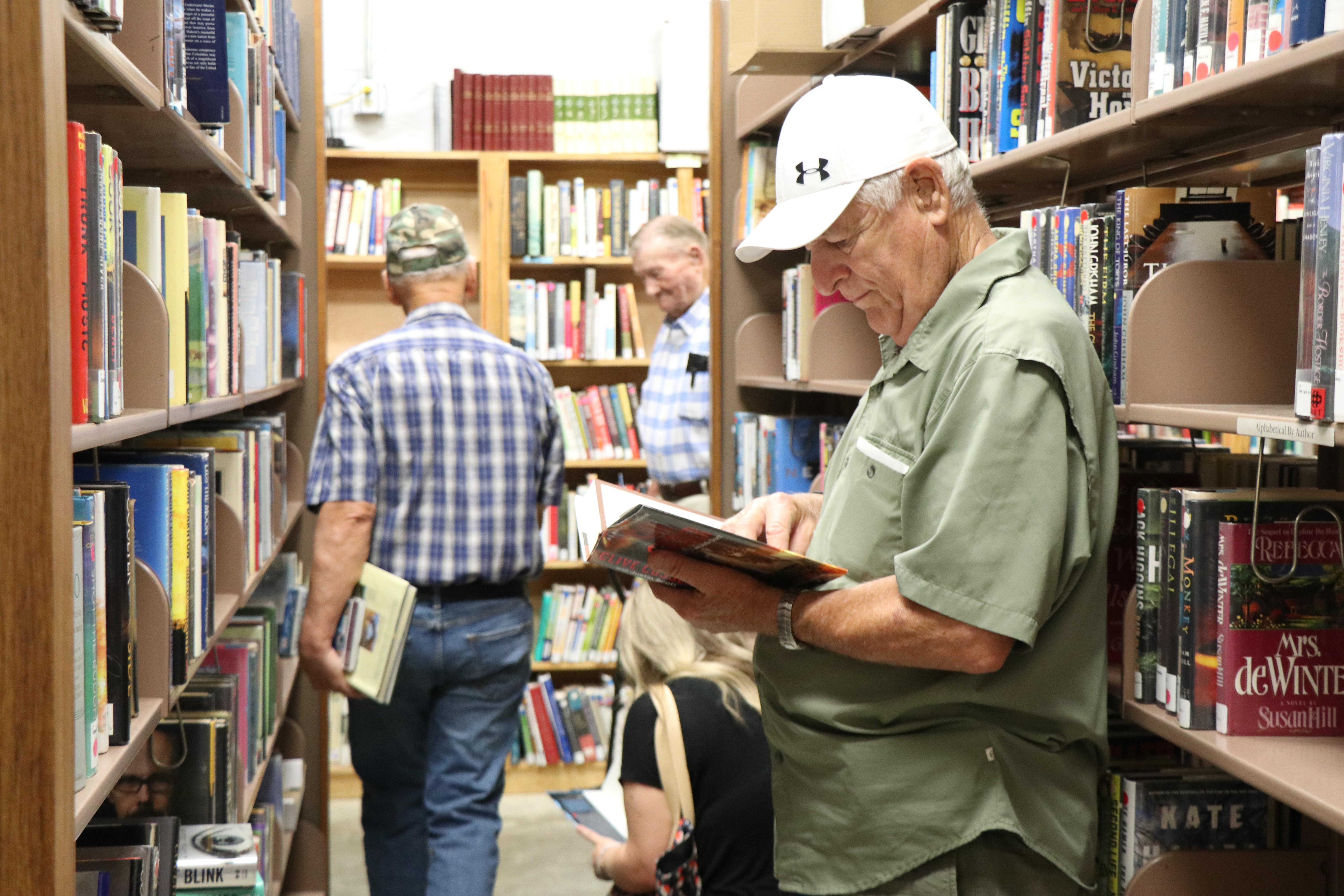 Two men stand in between bookshelves. One is looking down at a book.