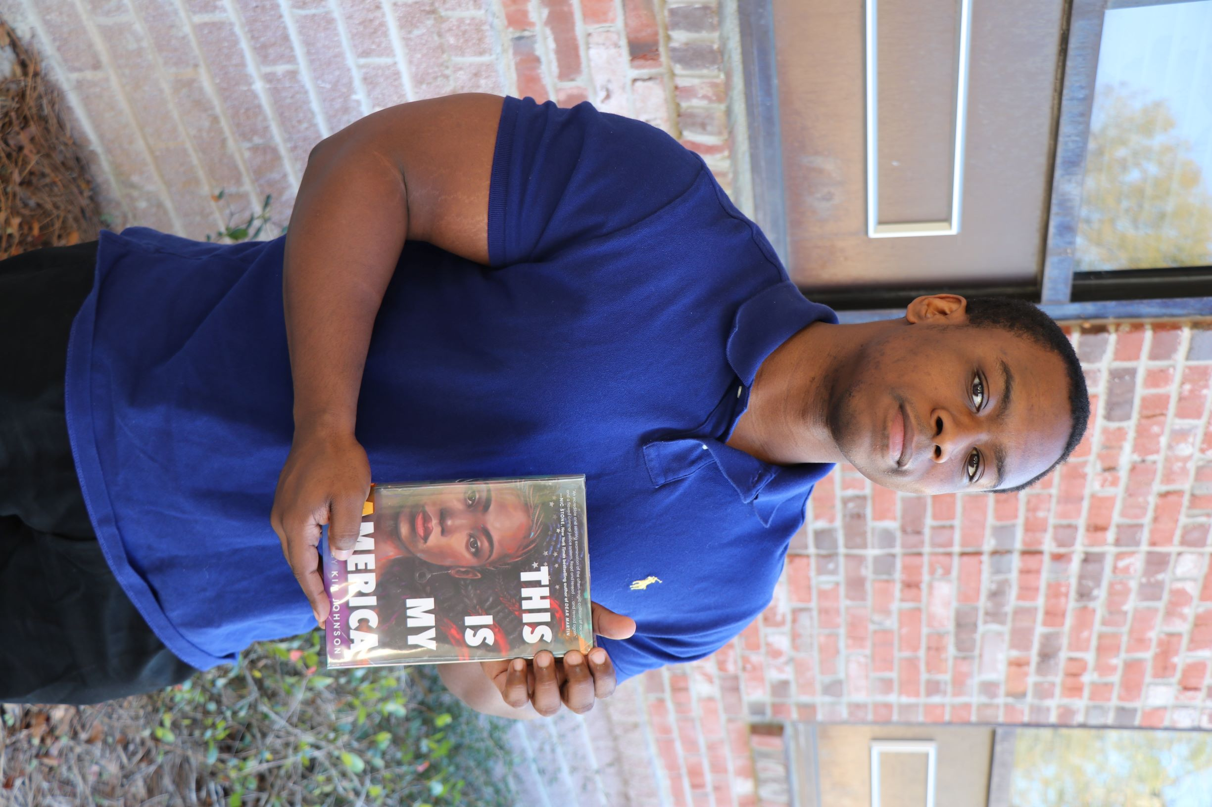 A man stands in front of a brick wall. He is holding the book This Is My America.