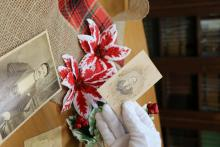 A gloved hand holds an old black and white photo. More old pictures lay on a table decorated with burlap and flowers.