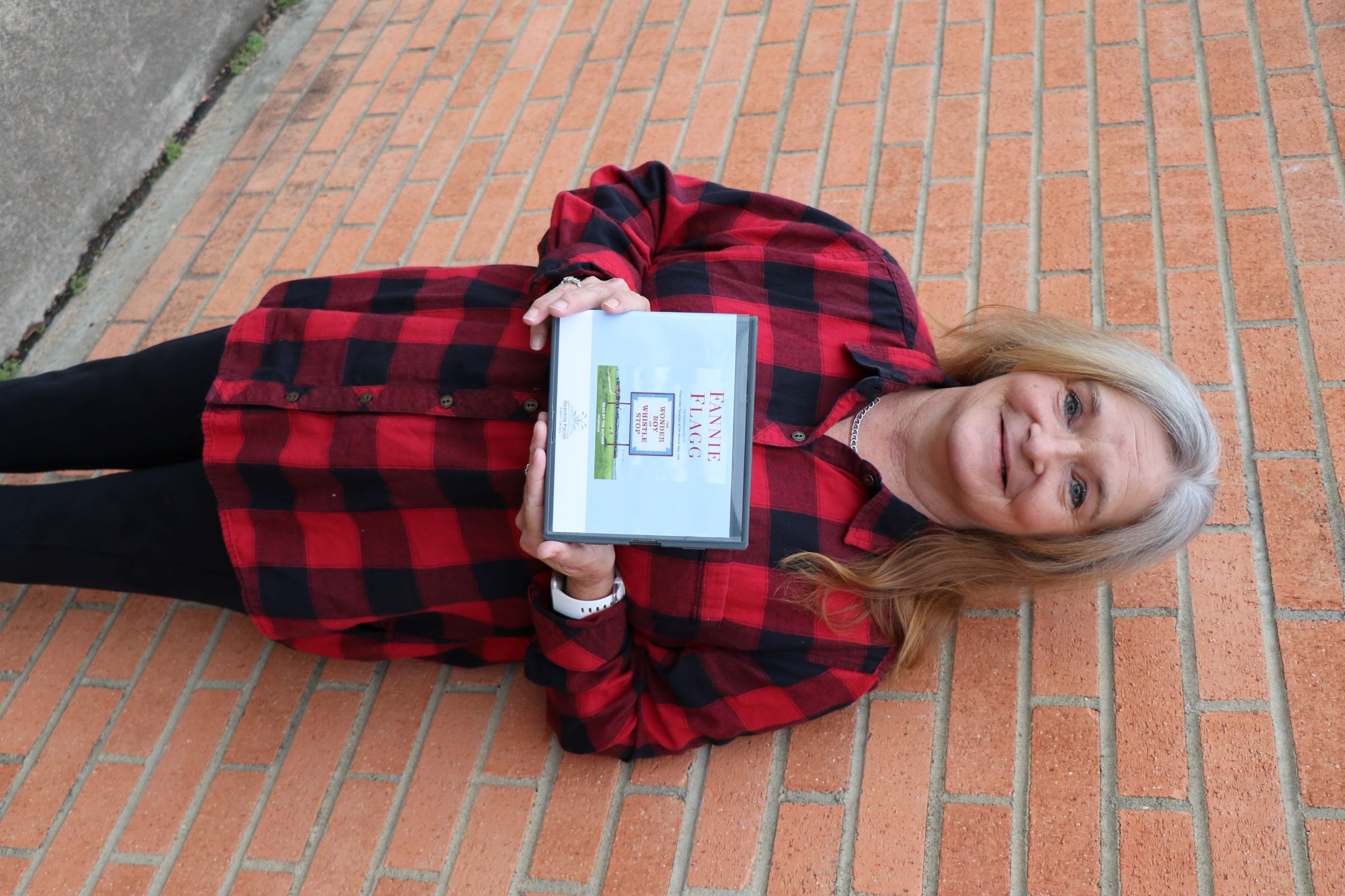 a woman stands in front of a brick wall. She is holding the book-on-CD, The Wonder Boy of Whistle Stop by Fannie Flagg.